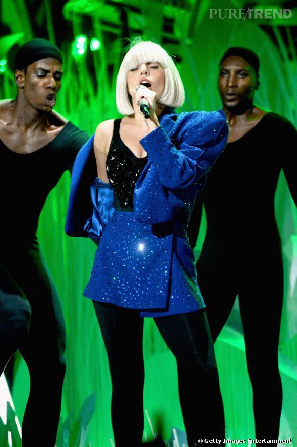 En un pas de danse, la chorégraphie prévoit l'habillage de la Gaga en blazer bleu. Un danseur lui met une perruque platine au carré.