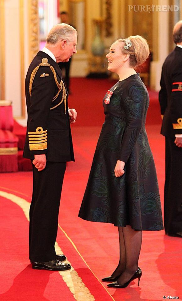 Adèle reçoit sa médaille de l'Ordre de l'Empire britannique des mains du prince Charles, jeudi 19 décembre...