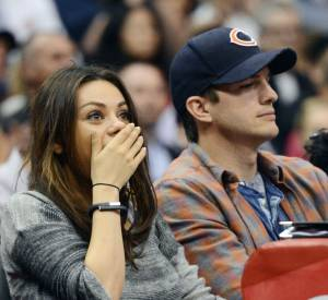 Mila Kunis et Ashton Kutcher s'embrassent au match de Los Angeles Clippers du 22 mars 2014 à Los Angeles.