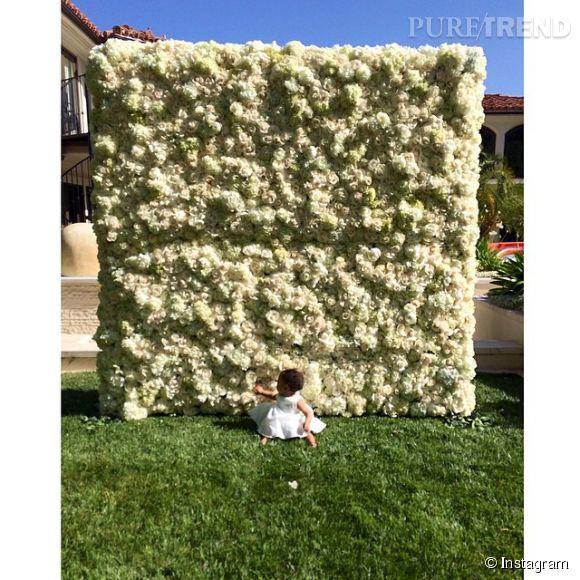 North West, la fille de Kim Kardashian et Kanye West, pose devant un mur de fleurs.