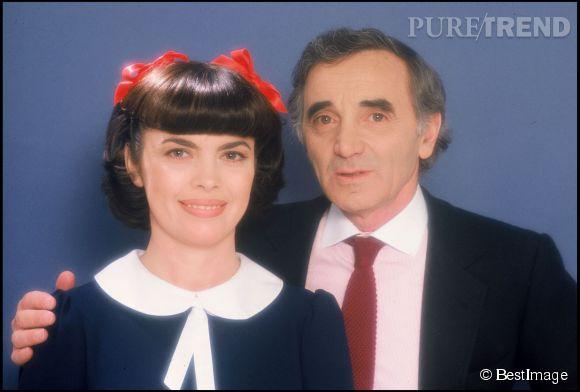 Aux côtés de Charles Aznavour en 1983, Mireille Mathieu a des airs de petite écolière avec ses deux nœuds rouge dans les cheveux.