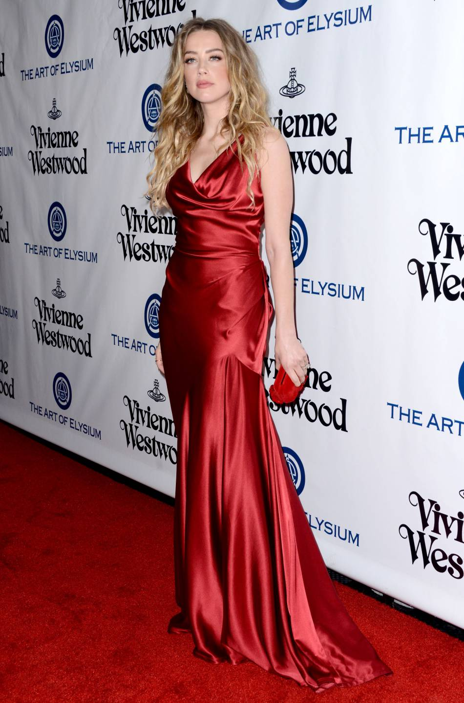 Amber Heard, radieuse dans sa robe moulante, couleur rouge passion.