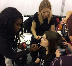 Make-up et coiffure en même temps pour les mannequins en backstage.