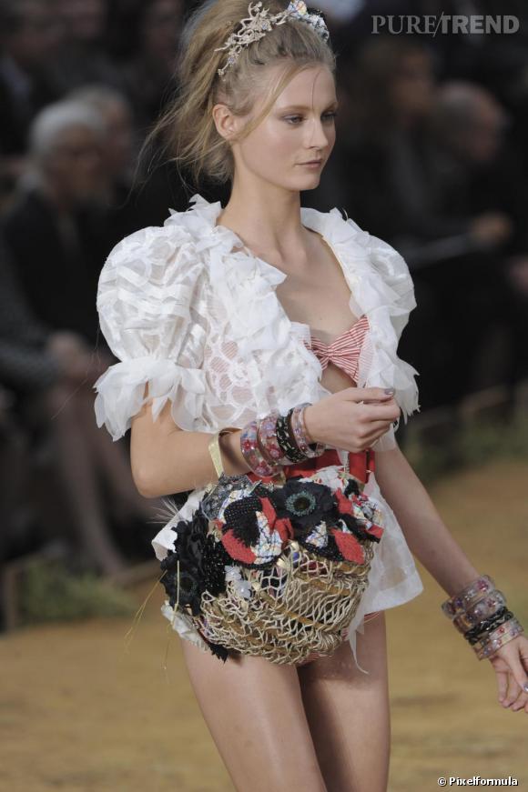 Défilé Chanel Printemps-Eté 2010  Première tendance forte : le panier. Chanel l'orne de fleurs en tissus dans l'esprit belle des champs.
