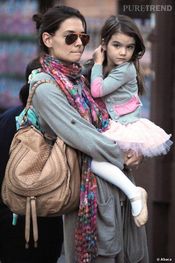 Marcie à l'épaule, sa fille dans les bras, et Ray Ban sur le nez, Katie mixe confort et tendance avec goût.
