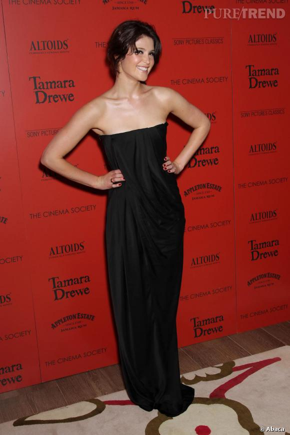 Simple et glamour elle mixe longue robe noire bustier et vernis rouge.