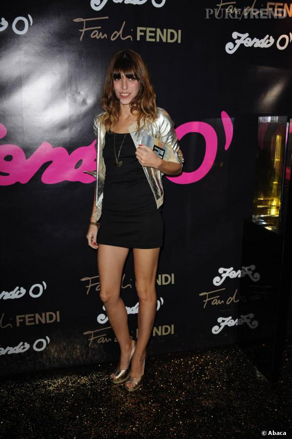 Courte robe noire et veste argentée, Lou  s'offre un look très bling montée sur des sandales dorées.