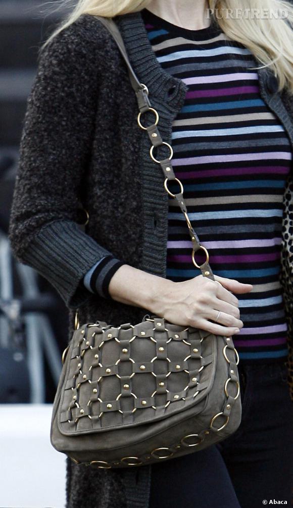 Originale, sa besace kaki à anneaux offre un peu de relief et style à une tenue assez ordinaire.