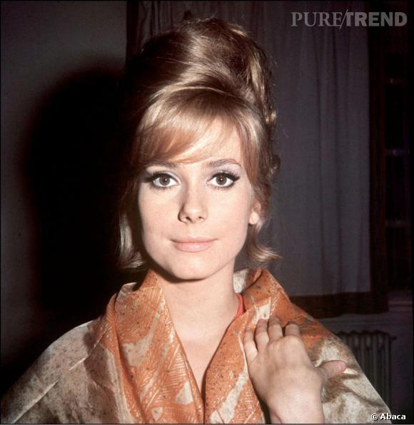1961, Catherine passe au blond qui fera sa renommée. Une frange portée sur le côté et quelques mèches s'échappent de son chignon haut, totalement glamour.