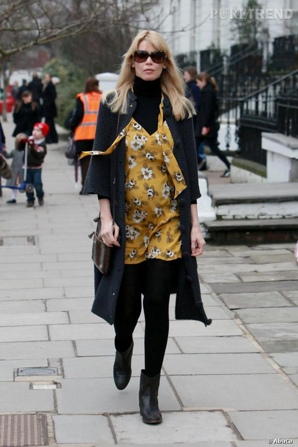 Claudia Schiffer,  icône de mode mais pas fashion victim, ne sacrifie pas son confort au style. Collants opaques, chaussures plates et grosse maille, une formule gagnante pour être à l'aise dans sa petite robe en soie imprimée jaune flashy. On adore.