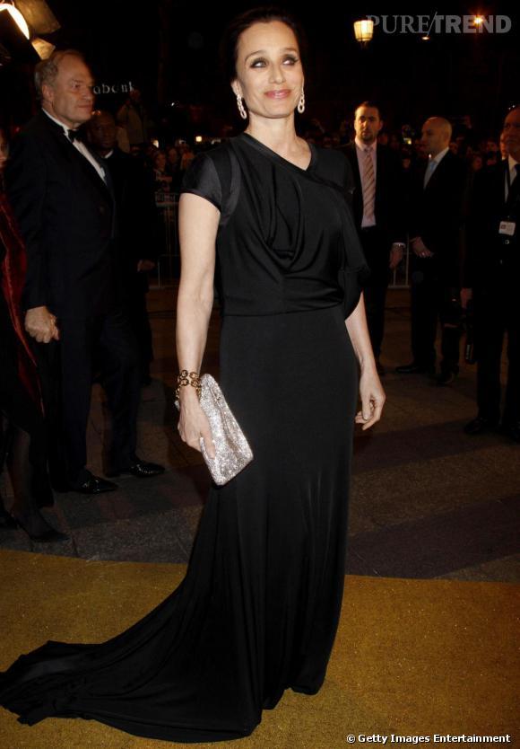 Longue robe noire fluide et drapée pour l'actrice lors des Césars, à laquelle elle donne une touche glitter avec des accessoires brillants.