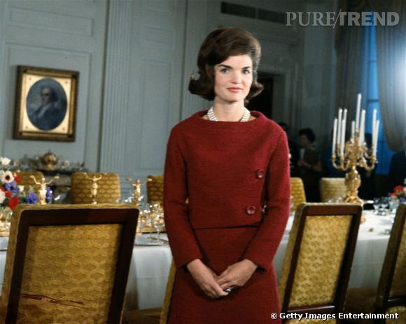 Coiffure impeccable, double rangée de perles au cou et robe en laine minimaliste : une démonstration du look de Jackie Kennedy dans toute sa splendeur.