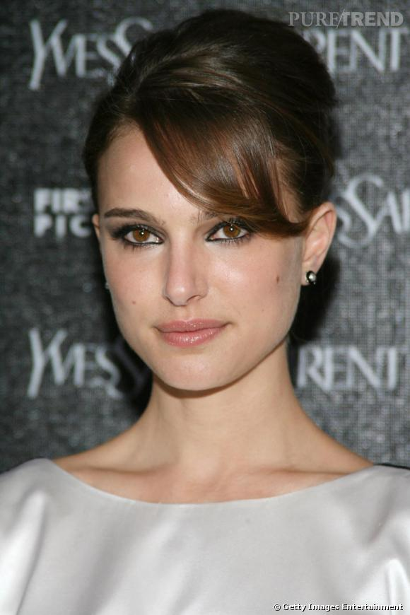 Natalie Portman mise sur le chic d'un chignon façon  Audrey Hepburn  impeccablement lissé. Et pour faire la différence, elle opte pour la frange-mèche sur le côté.