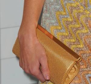 """Pour complèter sa tenue, une pochette dorée qui donne une petite touche """"habillée""""."""