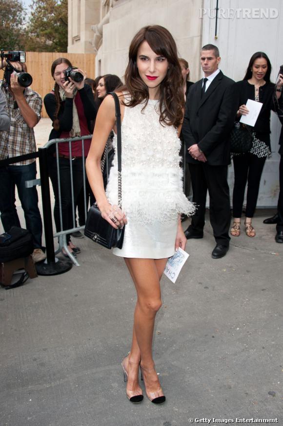 Trop belle en robe à plumes Chanel, sac Boy au bras.