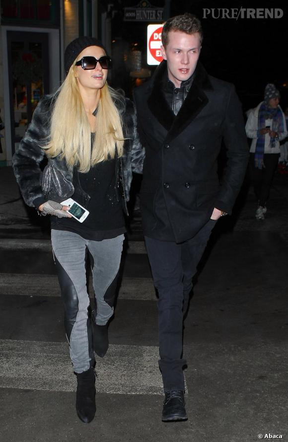 Paris Hilton à Aspen dans les bras de son boyfriend. Jean looké , bottines à talons et manteau en fourrure, on reconnaît bien la star !