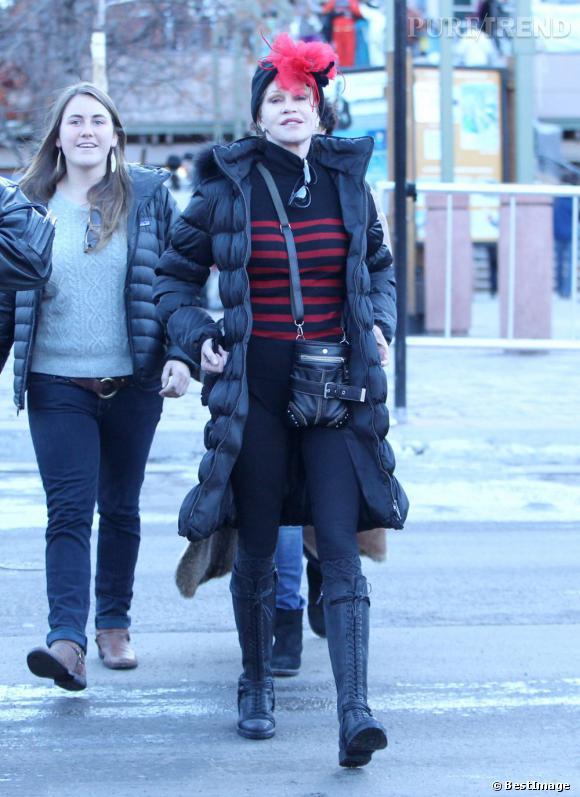 On retrouve les rues d'Aspen et la tenue très originale de Mélanie Griffith. Bonnet extravagant, chaussures à lacet montante et doudoune longue, il fallait oser.