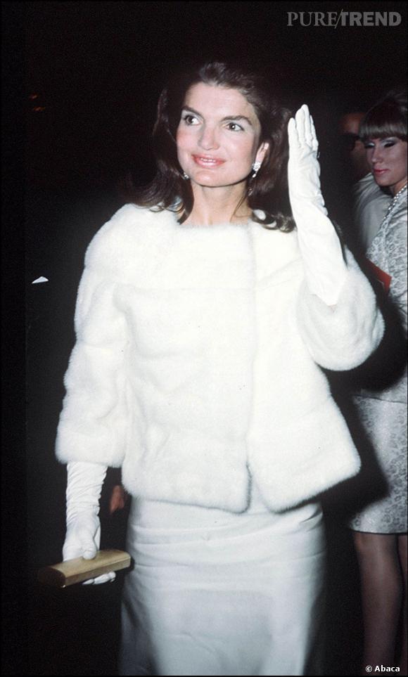 Jacqueline Kennedy, devenue Onassis après la mort de son mari en 1963, toujours aussi élégante dans un tailleur blanc, fourrure blanche et gants immaculés.