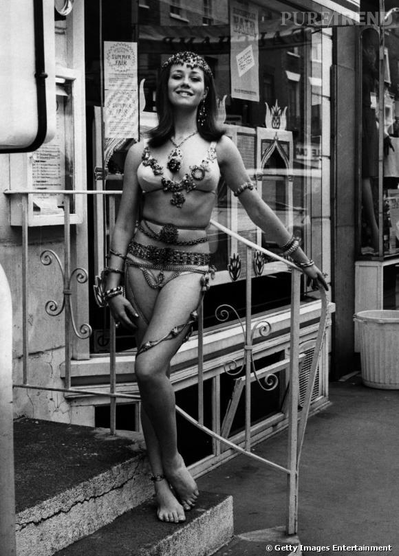 Une jeune femme pose, habillée seulement de sous-vêtements et de bijoux...