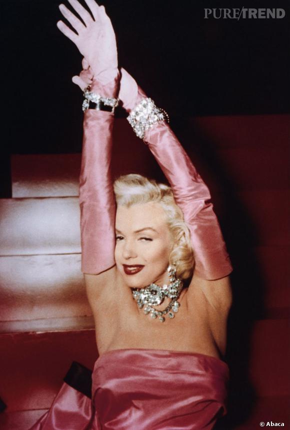 """Dans le film Les hommes préfèrent les blondes, Marilyn Monroe est une blonde explosive et croqueuse de diamants. Femme fatale jusqu'au bout des doigts, elle s'arme de gants en satin de soie pour encore plus de féminité. Pour l'anecdote, Wiliam Travilla avait cousu de discrètes paumes en coton à l'intérieur de ses gants """"peau d'ange"""" pour faciliter sa chorégraphie."""