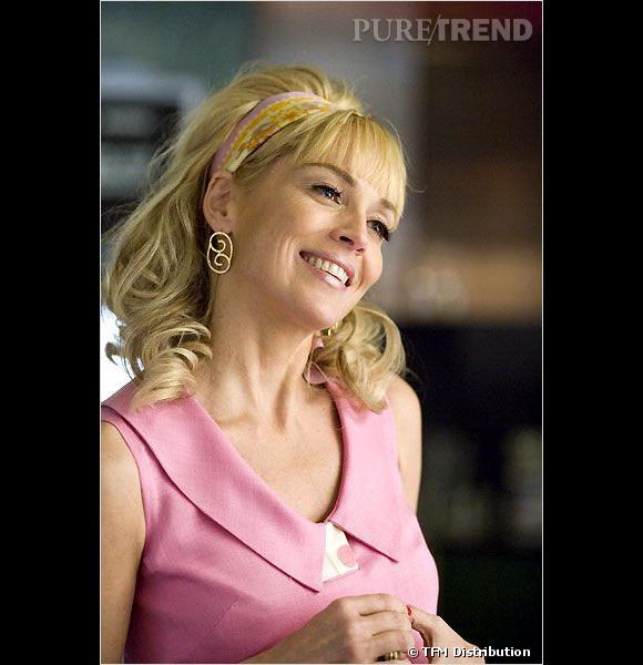 """Sharon Stone retrouve son blond dans """"Bobby"""", mais on dit non à la coiffure un brin cagole. Boucles grossières + foulard dans les cheveux + robe rose = too much."""