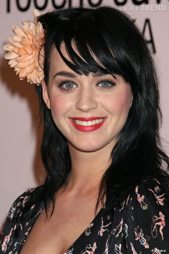 L'évolution capillaire de Katy Perry :  En mars 2008, la chanteuse commence sa carrière avec un carré long et une mèche sur le côté. La grosse fleur est en option.