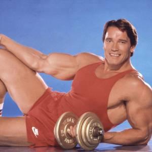 Arnold Schwarzenegger et son accessoire fétiche de l'époque, les altères.