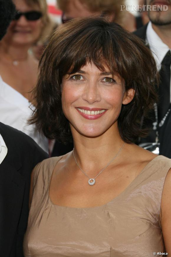 En 2009, Sophie Marceau opte pour un carré et une frange bien fournie et épaisse. Elle suit le mouvement naturel de ses cheveux.