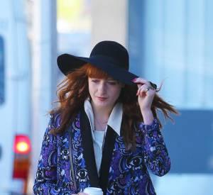 Florence Welch porte des bottines noires et un sac noir, pour un rendu rock et rétro.