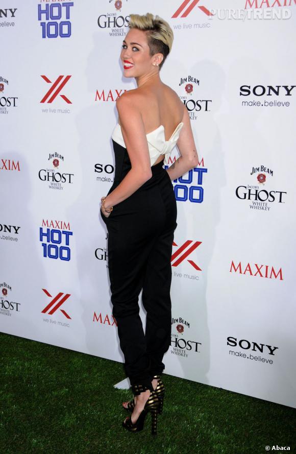 Miley Cyrus dévoile l'arrière de sa combinaison décorée d'un joli noeud.