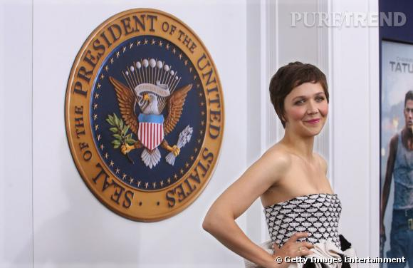 Maggie Gyllenhaal devant l'écusson de la Maison Blanche.