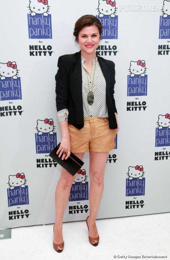 Tiffani Thiessen arbore un look rétro glam' avec un short en cuir camel et une blouse à pois.