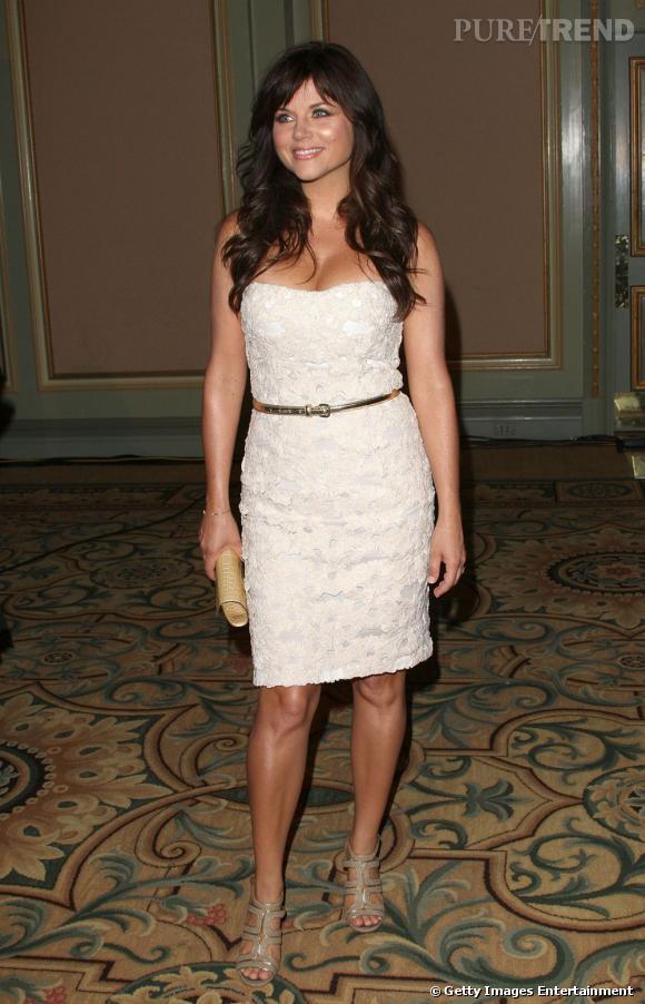 Tiffani Thiessen est sublime dans cette robe bustier en satin crème brodée de fleurs ton sur ton.