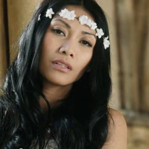 Longue robe blanche, couronne de fleurs : Anggun est l'innocence incarnée.