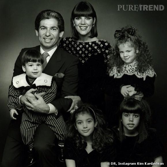 Photo de famille pour les Kardashian. Le père, Robert Kardashian pose avec le petit Robert Jr. dans ses bras et aux côté de sa femme, Kris Jenner. On retrouve la petite Khloe aux cheveux frisé, puis en dessous d'elle, Kourtney et enfin, en bas au centre, Kim Kardashian.