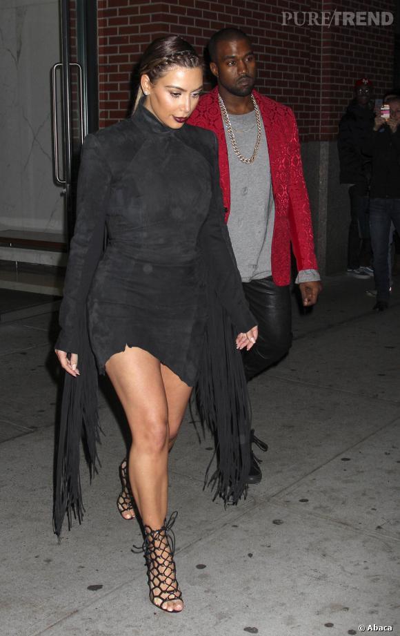 Tandis que Kanye West moule sa silhouette dans une mini robe en cuir frangée, Kanye West opte pour une veste rouge aux imprimés baroques.