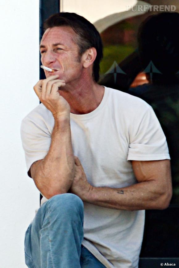 Clope au bec, blue jeans et bras tatoué : le look Sean Penn.