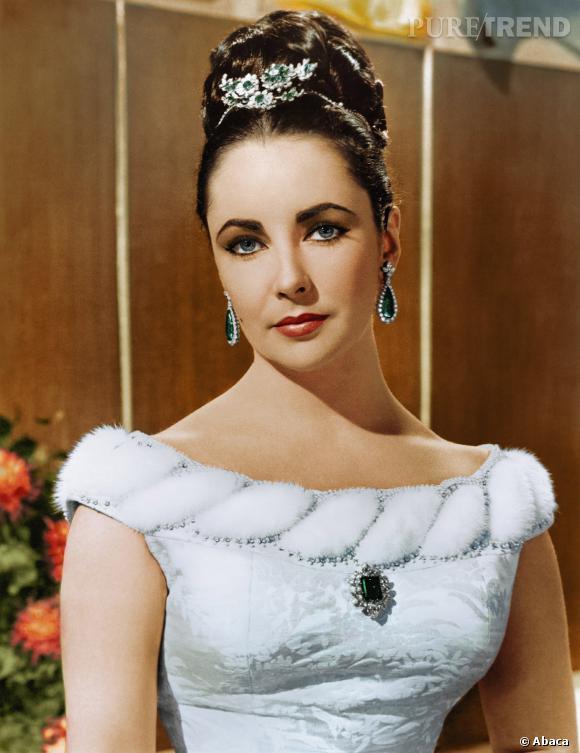 Elizabeth Taylor porte dans les cheveux une broche en diamants et émeraudes Bulgari, l'une de ses pièces phares. Elle affiche également ses boucles d'oreilles en émeraudes et diamants de la maison romaine.