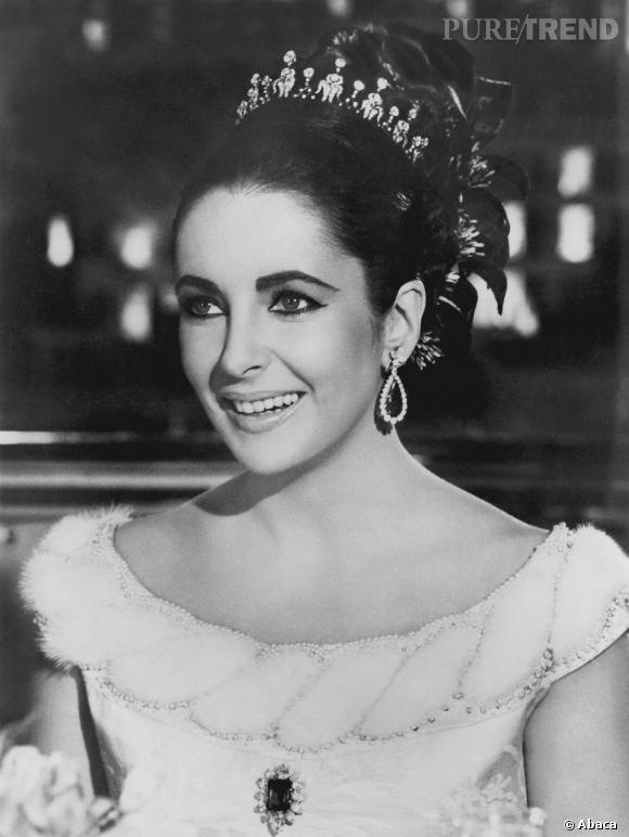 Elizabeth Taylor parée de boucles d'oreilles en diamants et émeraudes de chez Bulgari offertes par Richard Burton.