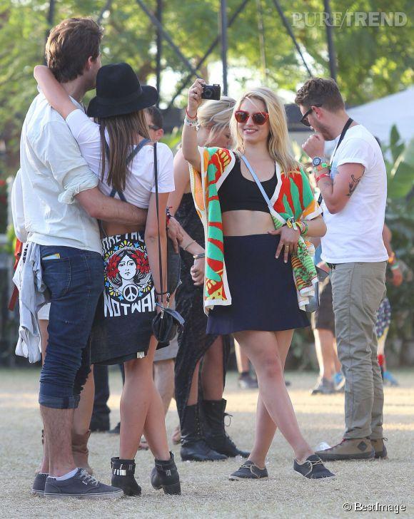 Dianna Agron porte le cropped top façon brassière noire et jupe taille haute. Elle ajoute du pep's avec un kimono à imprimé vif sur le campus de Coachella 2014.