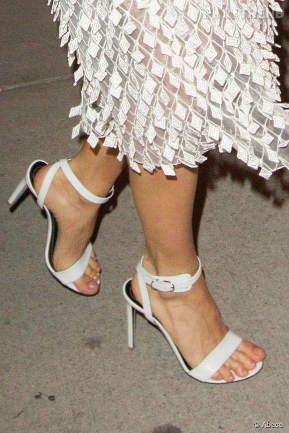 Sienna se juche sur une paire de sandales à talons.