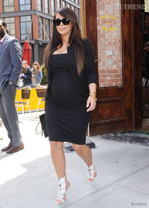 Petite robe noire moulante et sandales blanches à talons, une tenue qui met en valeur le petit ventre bien arrondi de la femme de Kanye West.