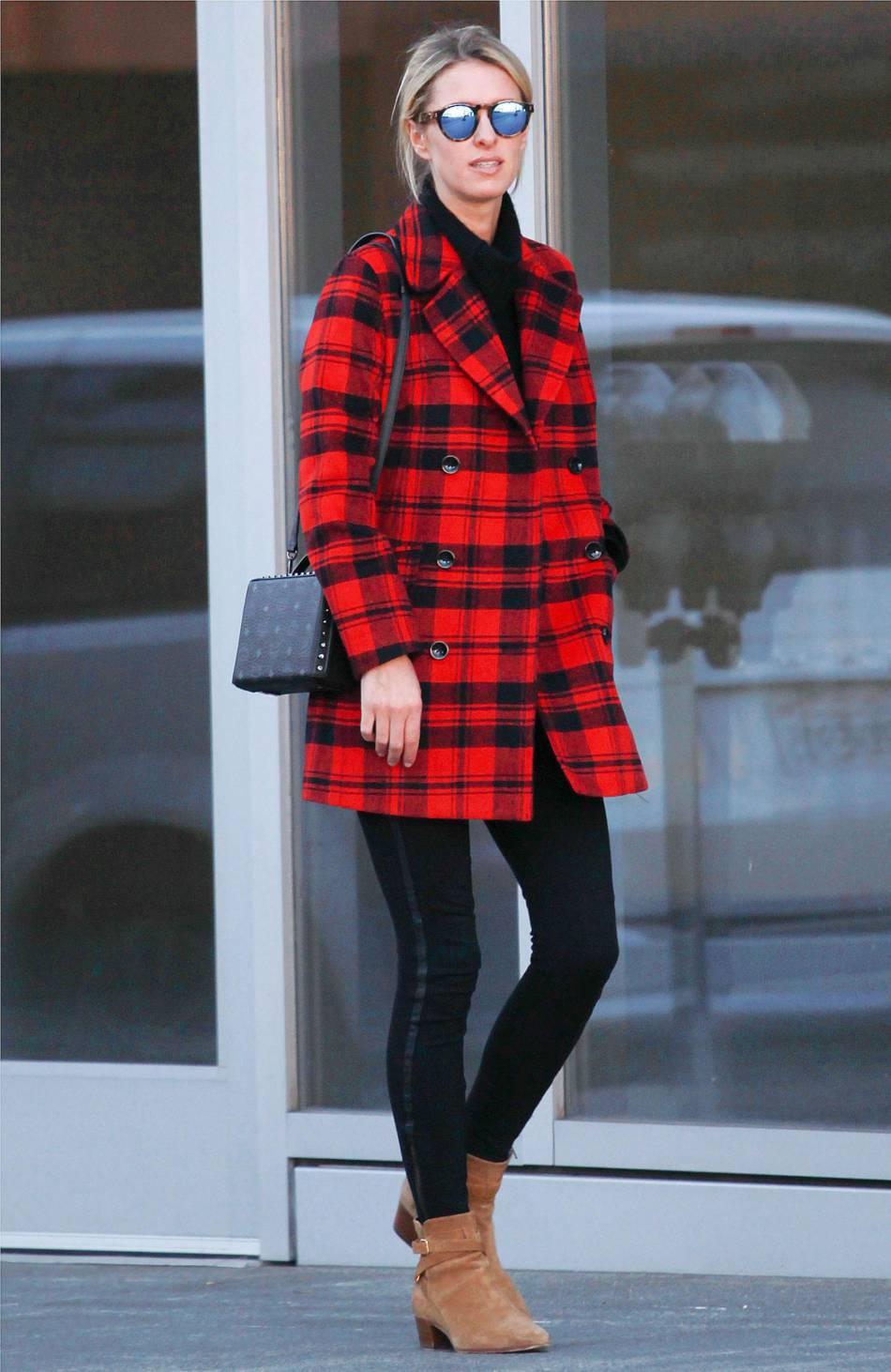 Nicky Hilton opte pour le manteau en tartan rouge vif.