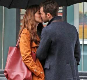 Anastasia Steele et Christian Grey échangent un baiser sous la pluie.