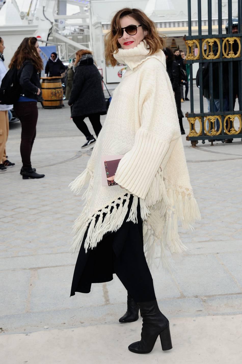 Clotilde Courau accessoirise son look avec une paire de lunettes de soleil et une bouche rouge.