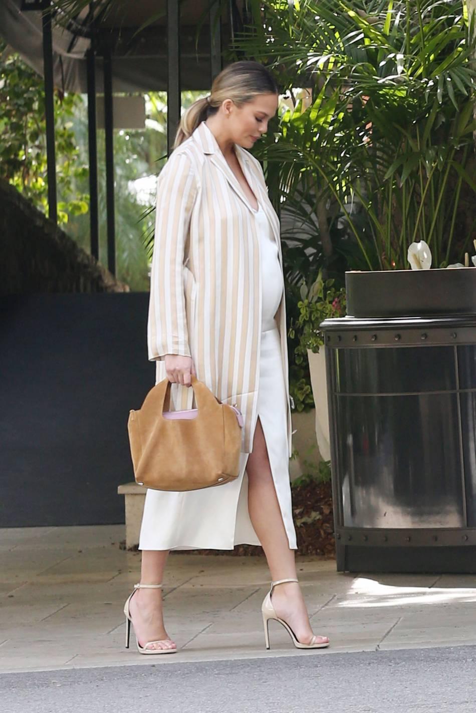 Chrissy Teigen opte pour un look de working girl glamour pour afficher son baby bump.