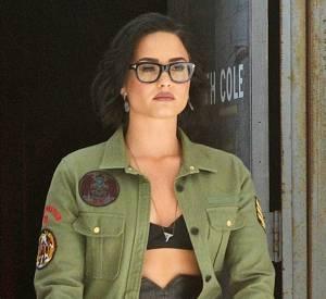 Demi Lovato porte une jupe crayon en cuir noir et une mini brassière accompagnée d'une veste militaire ample.