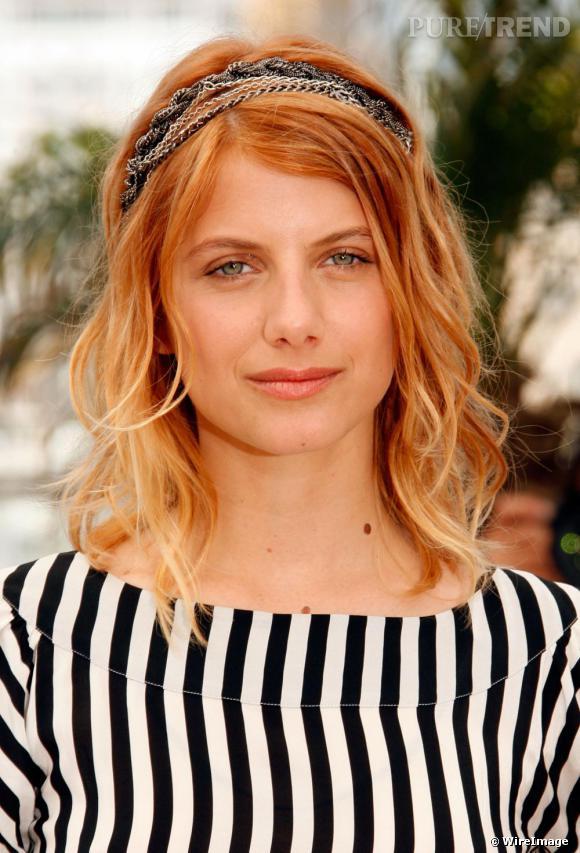 [people=1967] Mélanie Laurent [/people]  opte pour un bandeau composé de chaines en métal argenté, glissé dans ses cheveux blonds détachés. Un choix original et rock.