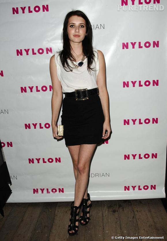 Débardeur blanc porté large, jupe noire taille haute ceinturée et spartiates à plateforme: Emma Roberts, toujours rock.