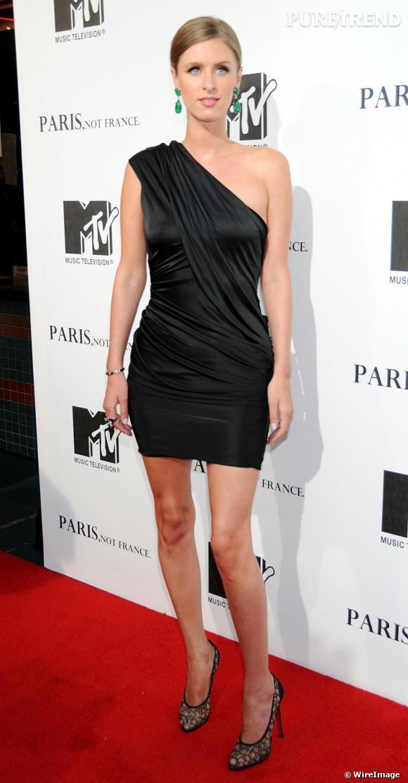 """Nicky Hilton opte pour une robe """"one shoulder"""" noire de la collection automne-hiver 2009 qu'elle accessoirise pour lui donner une allure preppy"""